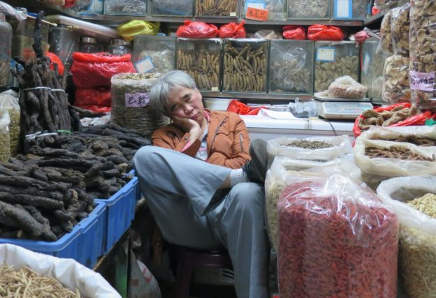 Chinese medicine vendor catching some zzz